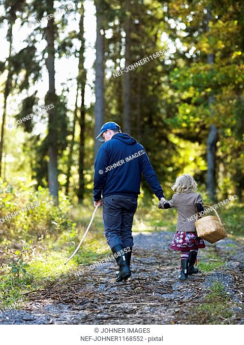 Father and daughter in forest picking mushrooms