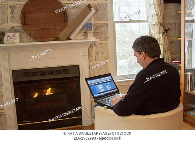 Caucasian man in his mid 40's working on his laptop from home by the fireplace in a cold day in North Carolina during a snow storm