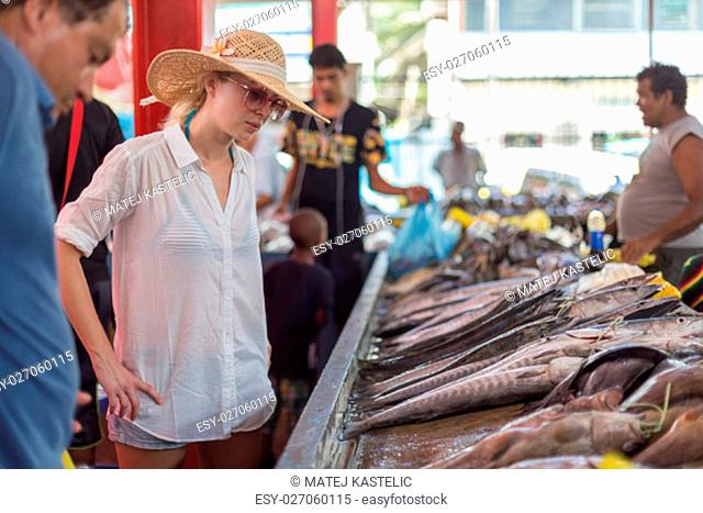 Female traveler wearing elegant colonial style white tunic and hat visiting traditional Victoria fish market on Seychelles islands