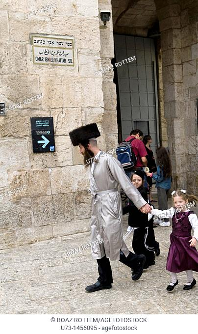 An Orthodox Jewish family walking into the old city of Jerusalem via Jaffa gate