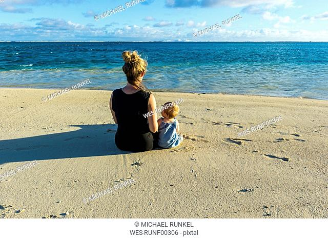 Cook islands, Rarotonga, Woman sitting with her baby on a white sand beach