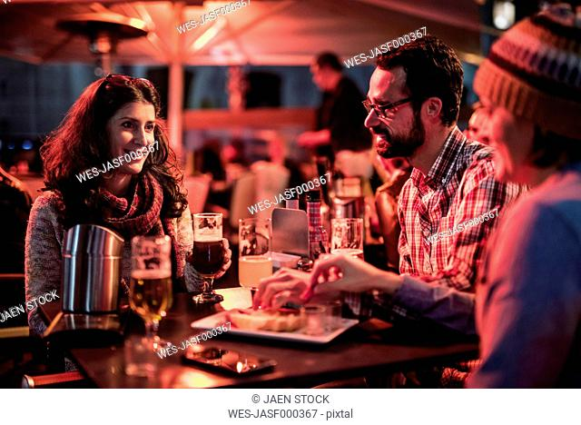 Three friends socialising at a pub at night