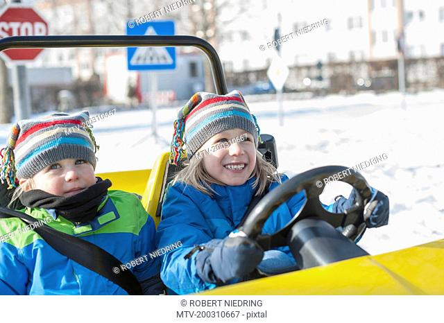 Boys driving electric toy car