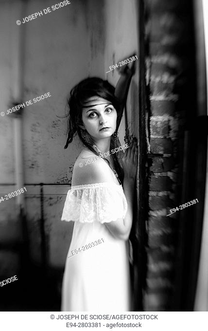 A 25 year old woman wearing a white dress looking at the camera standing in an abandoned building, black and white