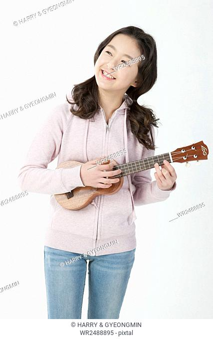 Smiling middle school girl playing an ukulele looking up