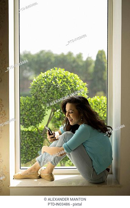 India, Smiling woman sitting on window sill and using mobile phone