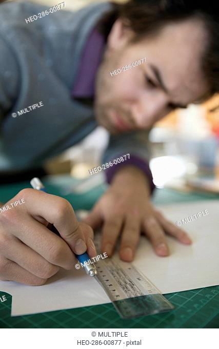 Close up of designer using ruler and bradawl on cutting mat
