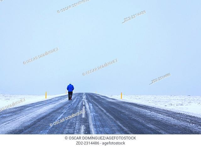 Man walking on frozen road in snowy landscape. Arnessysla. Iceland