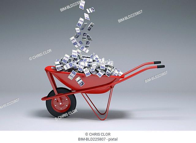 British pounds falling into red wheelbarrow