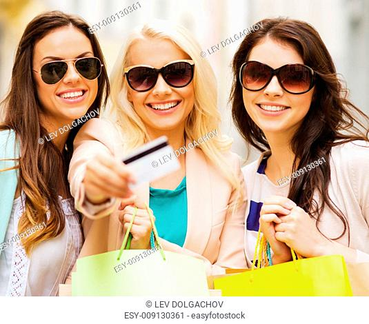 shopping and tourism concept - beautiful girls with shopping bags and credit card in ctiy