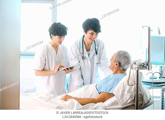 Patient in hospital room attended by a doctor, Hospital