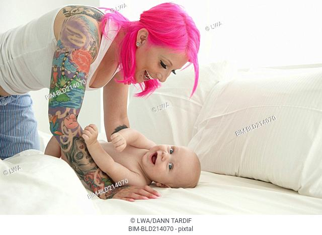 Caucasian mother with pink hair and tattoos playing with baby