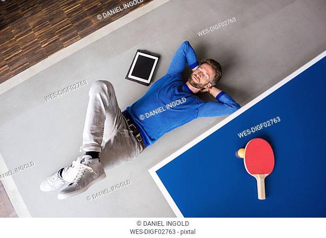 Man lying on the floor with tablet in break room of modern office