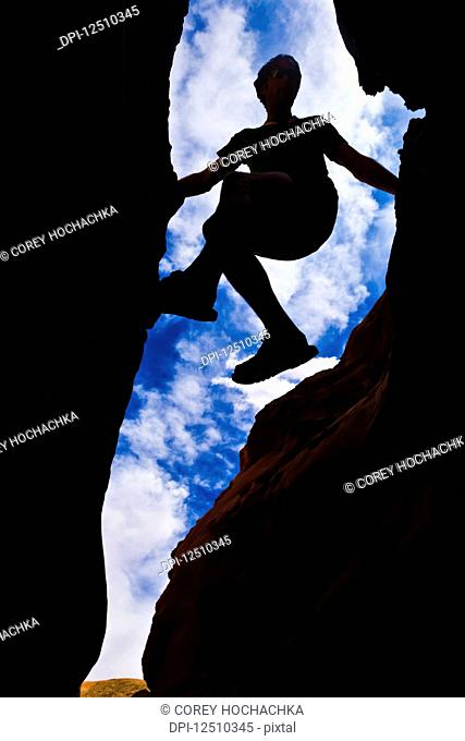 Looking upwards to the silhouette of a climber in a slot canyon in the desert; Hanksville, Utah, United States of America