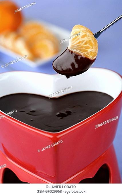 Heart-shaped chocolate fondue dipping a tangerine segment, close up