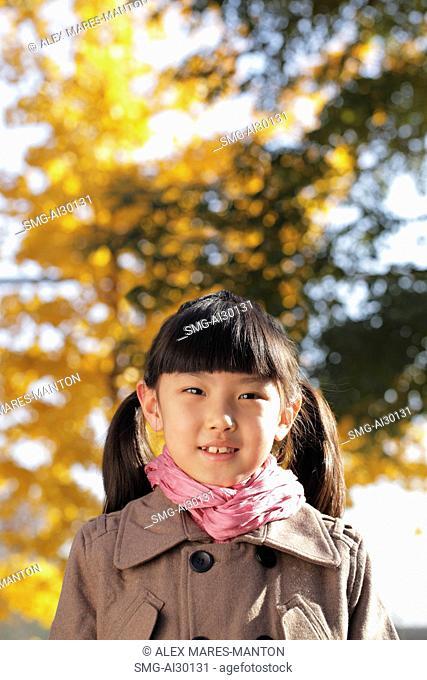 Head shot of young girl in coat outdoors
