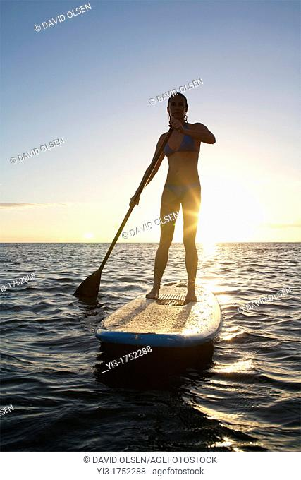 Female stand-up paddler at sunset at Maui, Hawaii with sunstar
