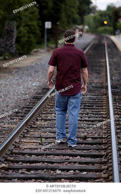 Man walking along the train tracks on a cloudy day