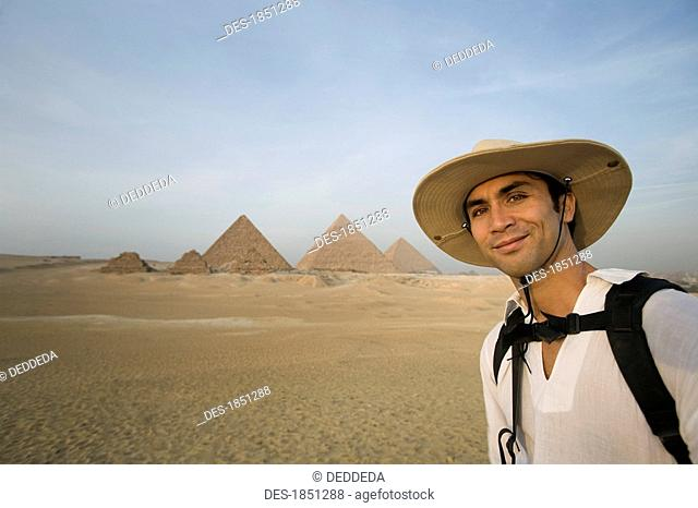 Man standing with Pyramids in background