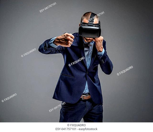 Male in a suit fighting with virtual reality glasses on his head