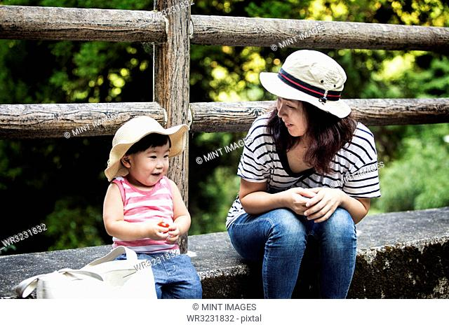 Smiling Japanese woman sitting next to little girl wearing sun hat, striped top and jeans