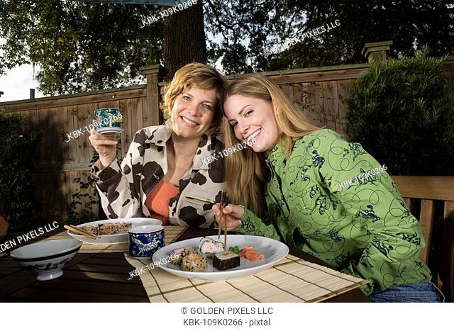 Mother and daughter eating sushi together