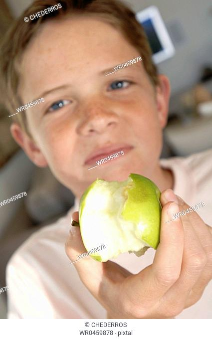 Portrait of a boy holding an eaten granny smith apple