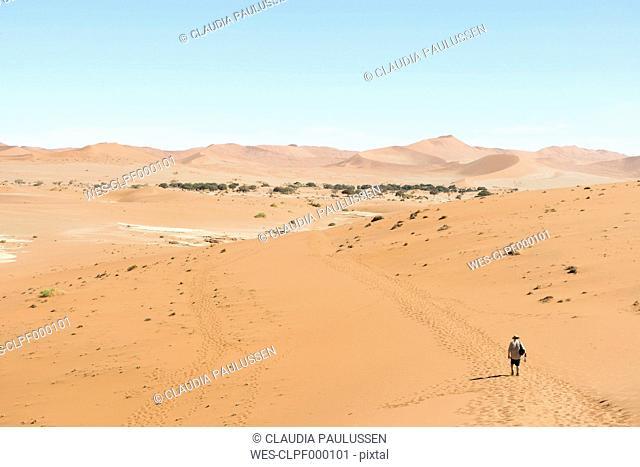 Namibia, Namib Desert, Namib Naukluft Park, Sossusvlei, man walking through the desert