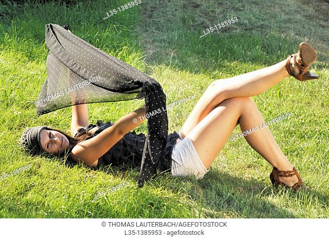 Young woman lying on the grass and playing with a cloth, summer, Germany