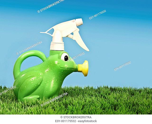Children's spray bottle on grass with blue background