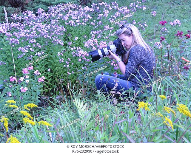 woman shooting photos in a field of flowers