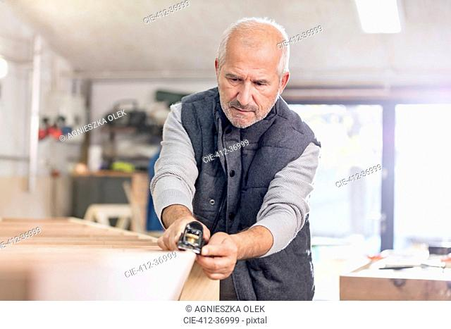 Focused senior male carpenter using jack plane on wood boat in workshop