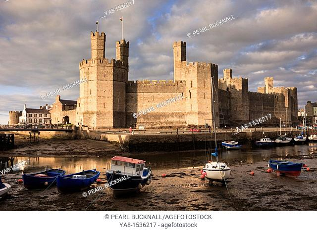 Caernarfon, Gwynedd, North Wales, UK, Britain, Europe  View of Edward 1st 13th century castle across Afon Seiont River estuary at low tide in the evening