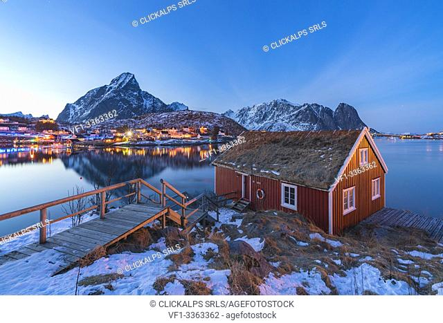 Traditional fishermen house above Reine Bay at dusk in winter. Reine, Nordland county, Northern Norway, Norway