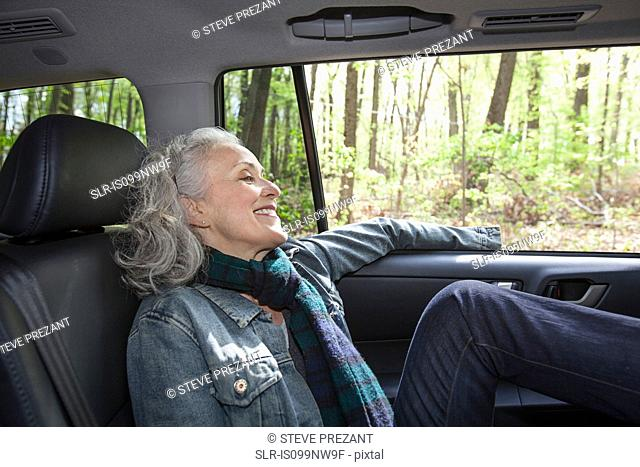 Senior woman relaxing in backseat of car