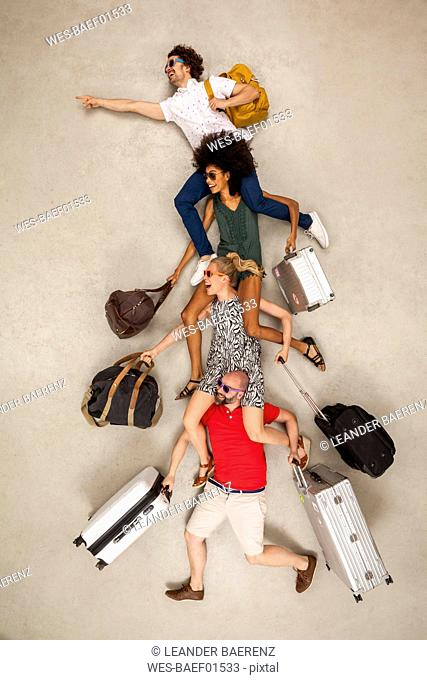 Tour group sitting on each other's shoulders, carrying luggage