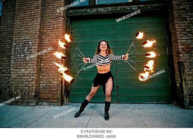Caucasian woman juggling fire on city sidewalk