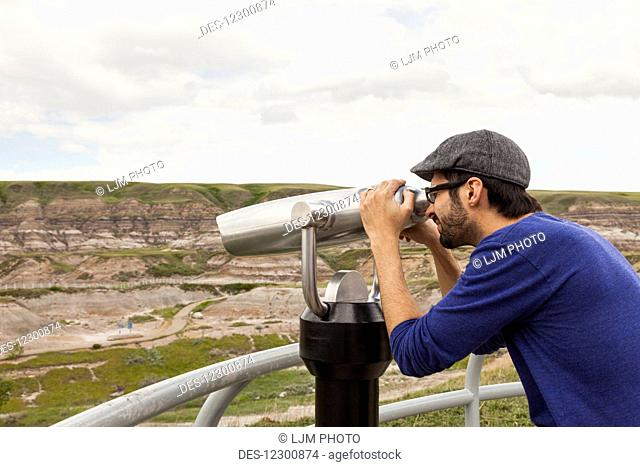 Man looking through binoculars outdoors at the Royal Tyrell Museum Of Palaeontology; Drumheller, Alberta, Canada
