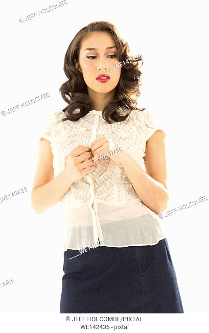 Beautiful young woman in white blouse and blue denim skirt, looking aside showing concern, deep thought