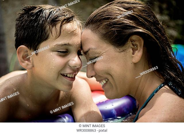 A woman and a boy cuddling in a swimming pool