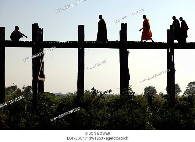 Myanmar, Mandalay, Lake Taungthaman. Monks Crossing U Bein Teak Bridge across Taungthaman Lake in Myanmar
