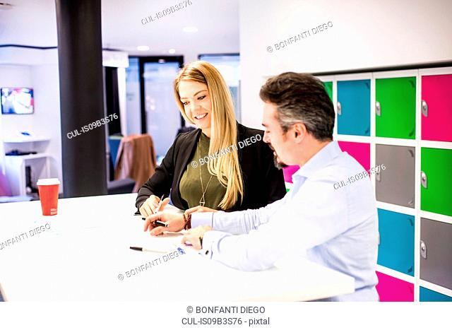 Businesswoman and man having brainstorming meeting in office