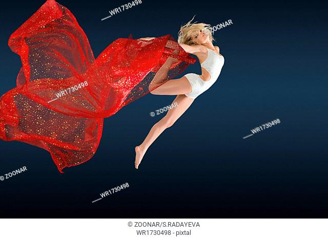 Woman jumping with silk fabric