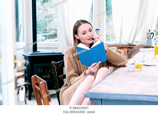 Woman sitting at dining table eating blackberries reading book