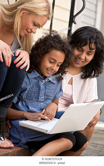 Hispanic girl using a laptop with her mother and sister