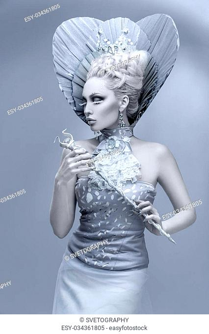 Portrait of beautiful young woman dressed as winter queen. Creative makeup. Over grey background. Copy space
