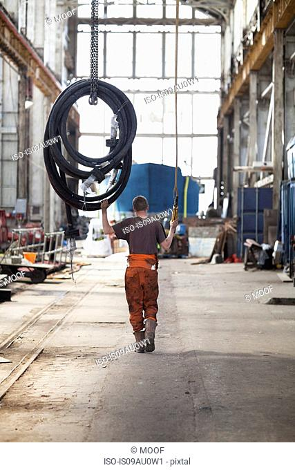 Rear view of worker pulling piping on winch in shipyard workshop