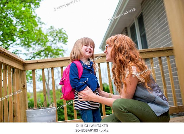 Mother and daughter standing on porch