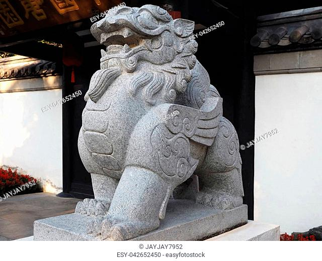 A sculpture of stone lion guarding in front of the shrine