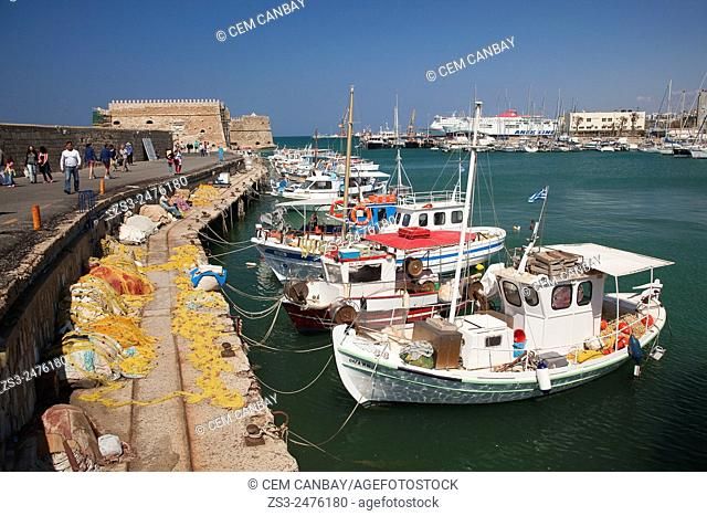 Fishing and sailing boats moored in Heraklion harbour with the old Venetian fortress at the background, Heraklion, Crete, Greek Islands, Greece, Europe